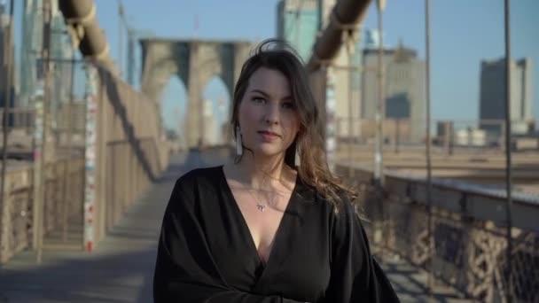 Žena v černém dlouhé tekoucí šaty procházky na Brooklyn Bridge v New Yorku.