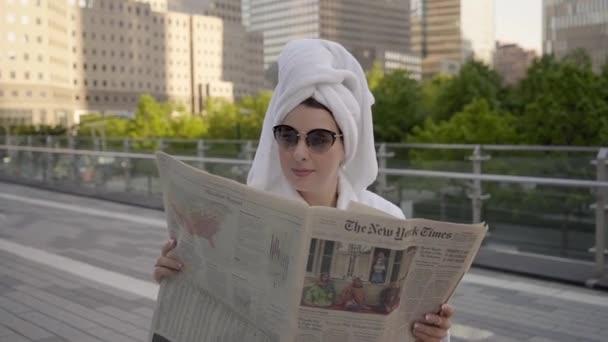 NEW YORK, USA - 18. května 2021: Dívka v županu a ručníku na hlavě s novinami.
