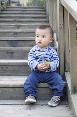 Cute Chinese baby boy playing outdoors