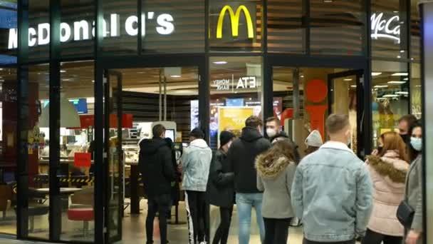 PRAHA, ČESKÁ REPUBLIKA, 22. PROSINCE 2020: Koronavirová maska obličej McDonalds fast food restaurace občerstvení bar shop nákupní centrum, vpředu čekající lidé dav covid-19, na sobě ohnisko respirační