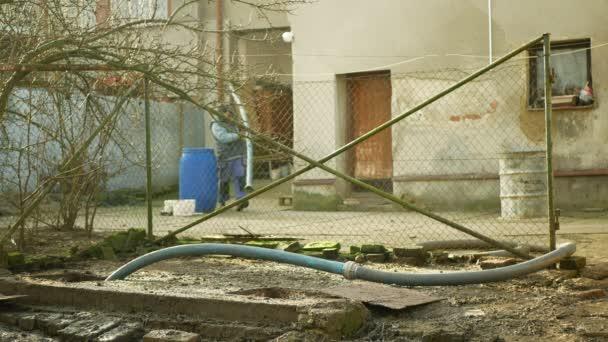OLOMOUC, TSCHECHISCHE REPUBLIK, 20. JANUAR 2021: Sickergrube, die unter Druck in einen Saugschlauch eines Tankwagens gepumpt wird. Menschen Arbeiter Häuser Dorf, Sumpf enthält Schmutzschlamm Abwasser