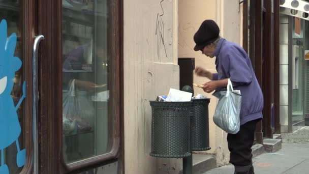 BRNO, CZECH REPUBLIC - JULY 16, 2015: Authentic homeless woman looking and eats food from the trash bin