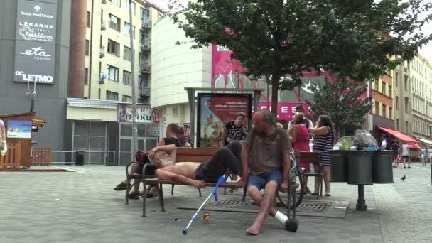 Brno, Česká republika - 1 září 2015: autentické emoce bezdomovec starší spí, probouzející a žere konzervy, Jižní Morava, Evropa, Eu
