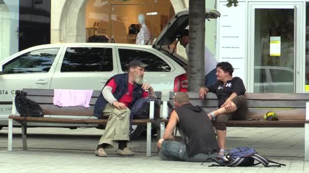 Brno, Česká republika - 16 července 2015: ulice život, dva muži a žena sedí na lavičce na náměstí, Jižní Morava, Evropa, Eu