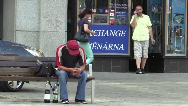 Brno, Česká republika - 16 července 2015: Street život, starší muž sedící na lavičce a další muž na telefonu, na náměstí, Jižní Morava, Evropa, Eu