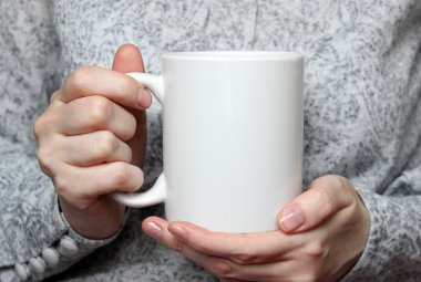 Girl is holding white cup in hands. White mug in woman's hands.