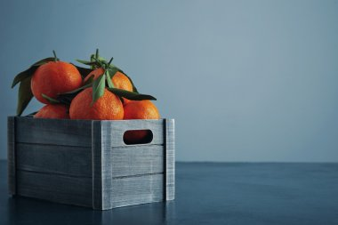 fresh tangerines in box with leaves isolated close