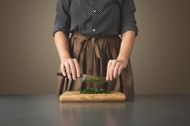 Woman holds knife above chopped green parsley