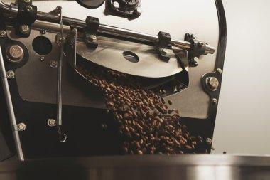 beans freshly baked fall inside roasting machine closeup