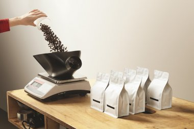 Hand pours roasted coffee on weight before package bag