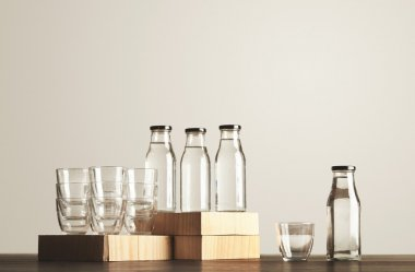 Glasses and bottles with water set on wooden table