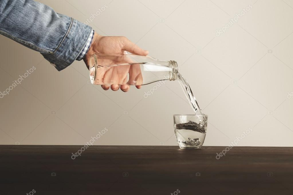 Hand pours clean water from bottle to cup
