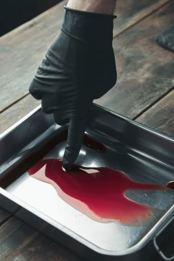 hand in black glove touches blood in steel stainer