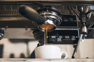 Fresh espresso coffee brewing through the bottomless portafilter