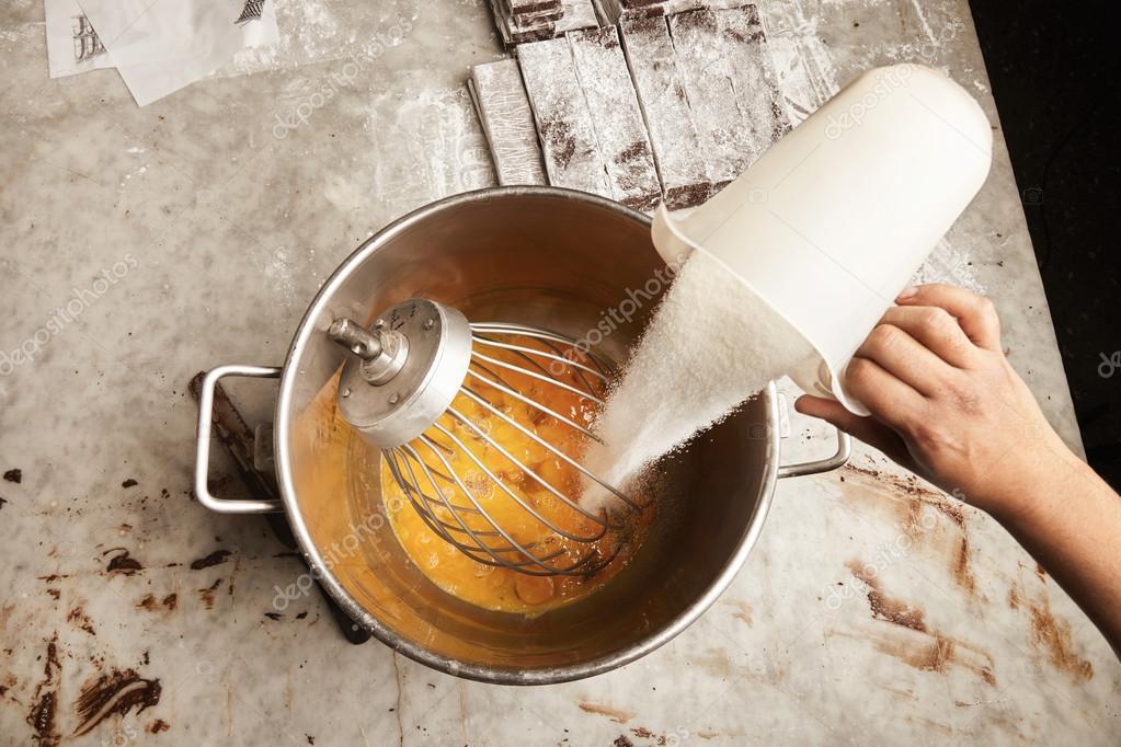 measure cup of sugar in big steel industrial bucket full of eggs