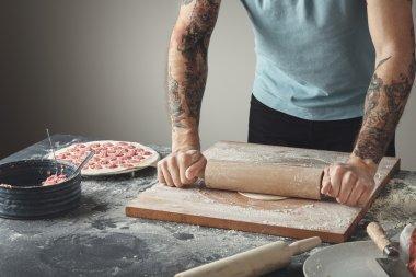Tattooed chief man cooks pelmeni