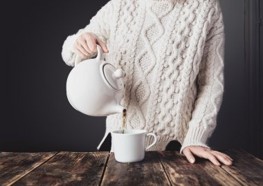 Woman in white sweater pours hot tea from big ceramic teapot