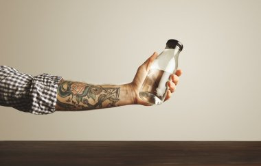 hand holds bottle with clean water