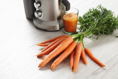metallic professional juicer with glass of carrot juice