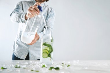 Bartender pours sparkling water in beverage like mojito