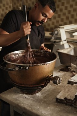 man cooks, mix melted chocolate with big whisk
