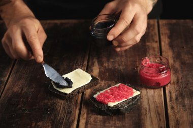 Man cooks  sandwiches with butter and caviar
