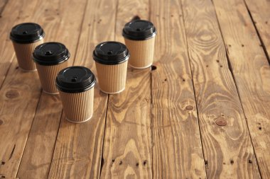 Five carton paper cups with black caps