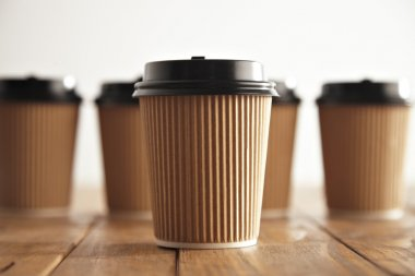 One focused paper coffee cup in front of unfocused others