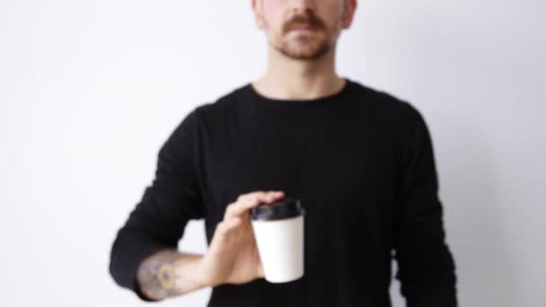 unfocused guy shows paper cup on camera