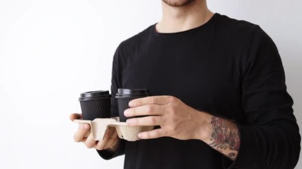 man in black presents paper cup on camera