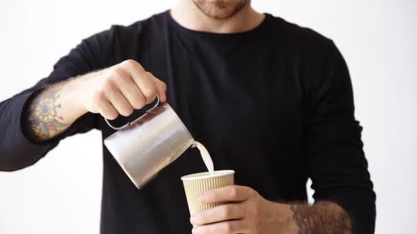 man pours milk from steamer pot to paper cup