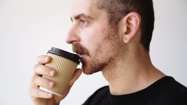 Bearded man drinks from paper cup