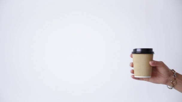 Woman hand moves brown paper cup