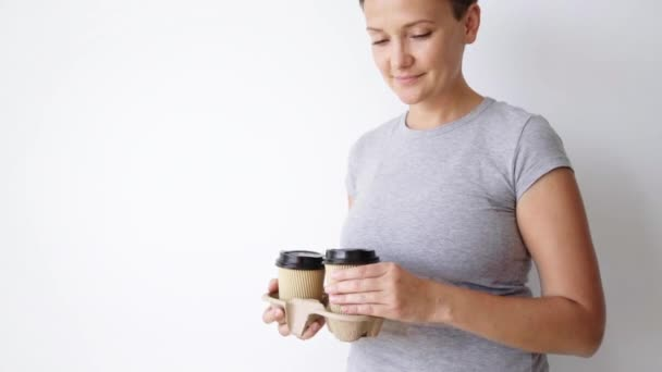 woman presents paper cup on camera