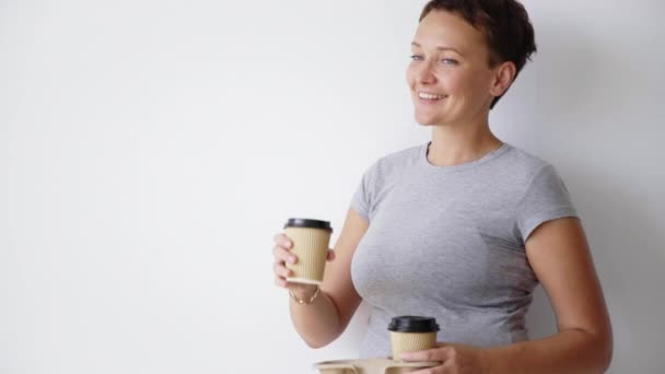 woman in t-shirt enjoys drink from paper cup