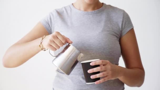 woman in blank t-shirt pours milk from metallic pot