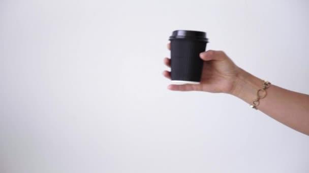 Woman hand gives cardboard take away cup