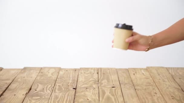 hand puts paper cup on rustic wooden table