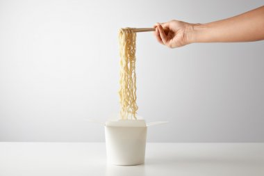 Hand picks up tasty boiled noodles
