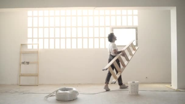 man brings stairs and starts to paints