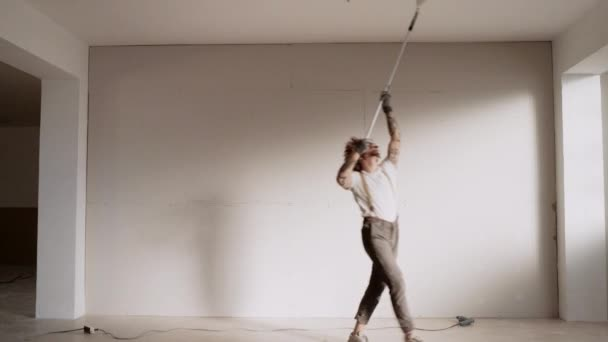 man dancing waltz while painting with brush roller