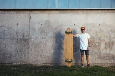 Tattooed man standing next to longboard