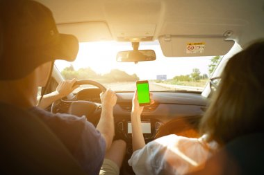 man holds hands on wheel and girl shows smartphone