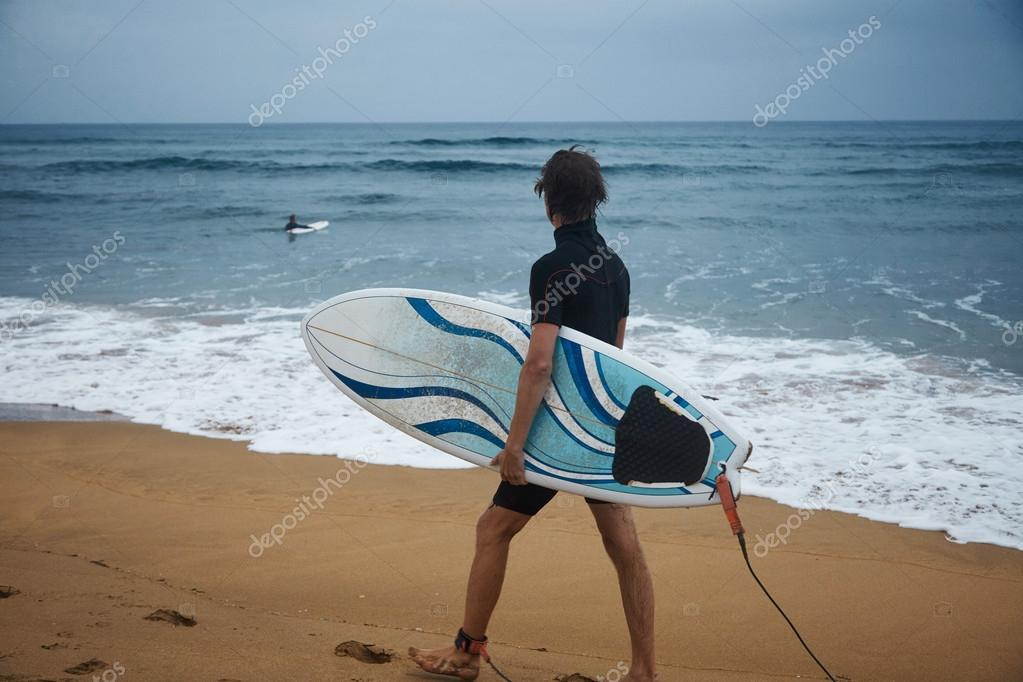 surfer walking on shore with board