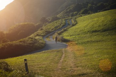 Surfer walking up hill on winding road