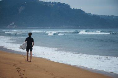 surfer in wetsuit walks along beach