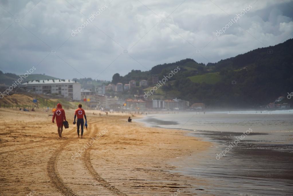 Lifeguards walking away on  beautiful empty beach