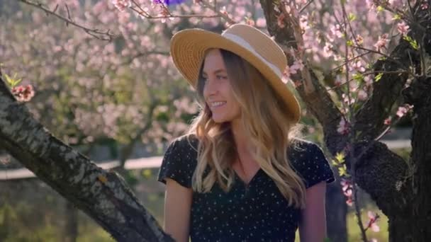 Beautiful young woman in fruit tree blossom garden