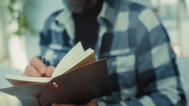 Mann in Großaufnahme schreibt in altes Notizbuch