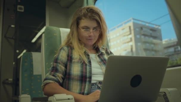 Fiatal nő dolgozik laptop, amikor ingázik vonattal
